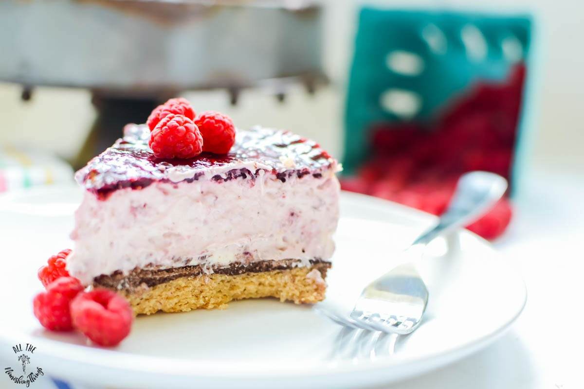 close up of slice of keto no-bake raspberry cheesecake on white plate with fork