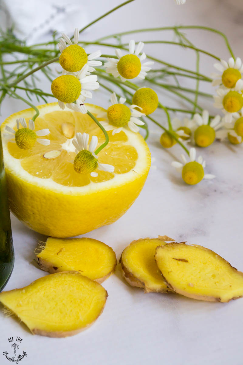 a lemon half with slices of fresh ginger and fresh chamomile flowers