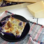black plate with cheesy purple potatoes and block of parmesan