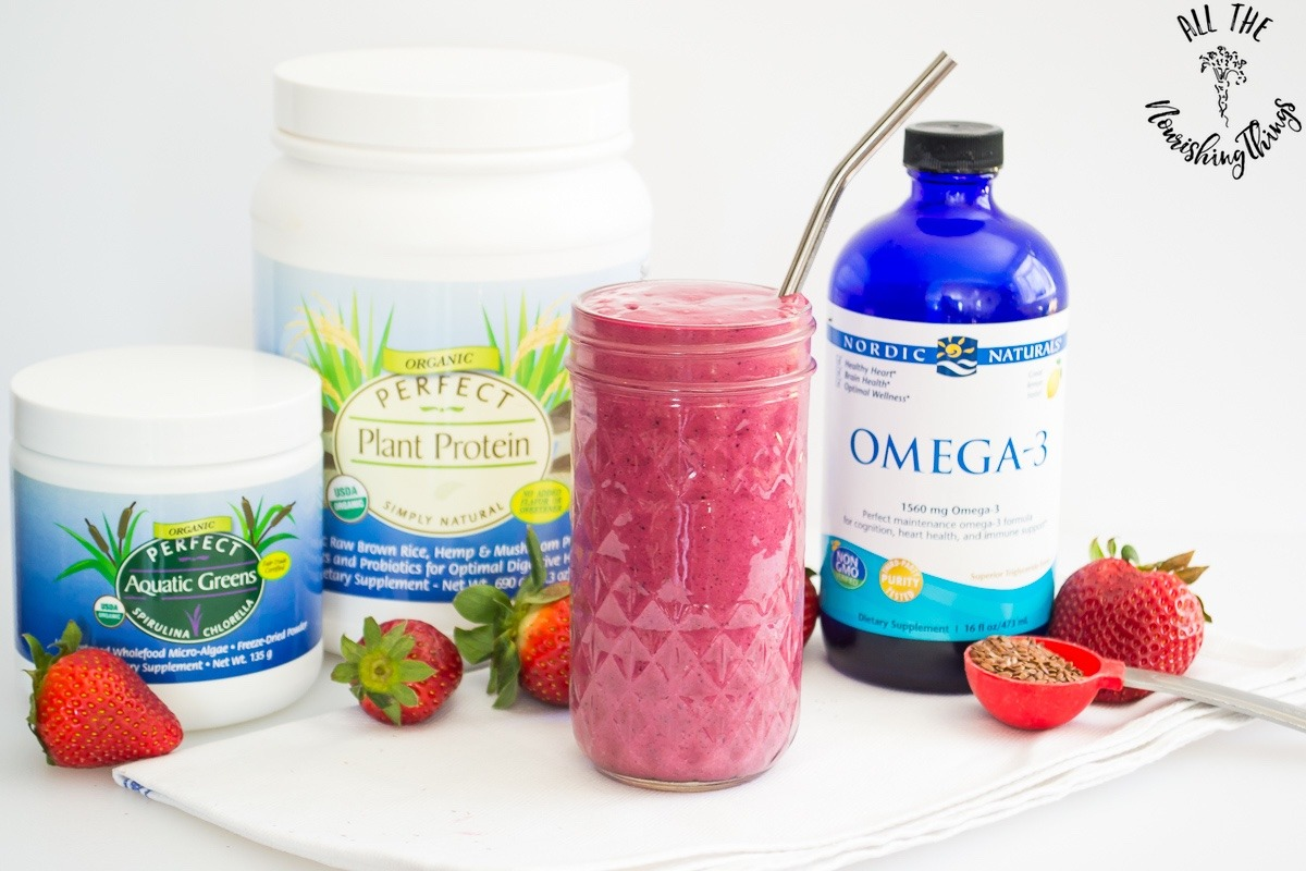 bright pink smoothie in front of supplements with strawberries around