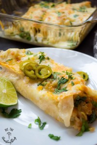 keto shrimp and greens enchilada with cheese on white plate