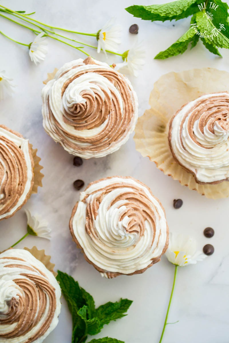 white and brown swirly frosting on keto chocolate chip cupcakes with mint leaves and daisy garnishes