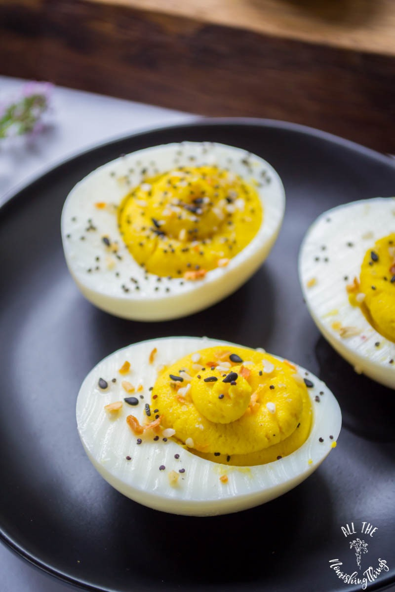 3 everything seasoning deviled eggs on black plate