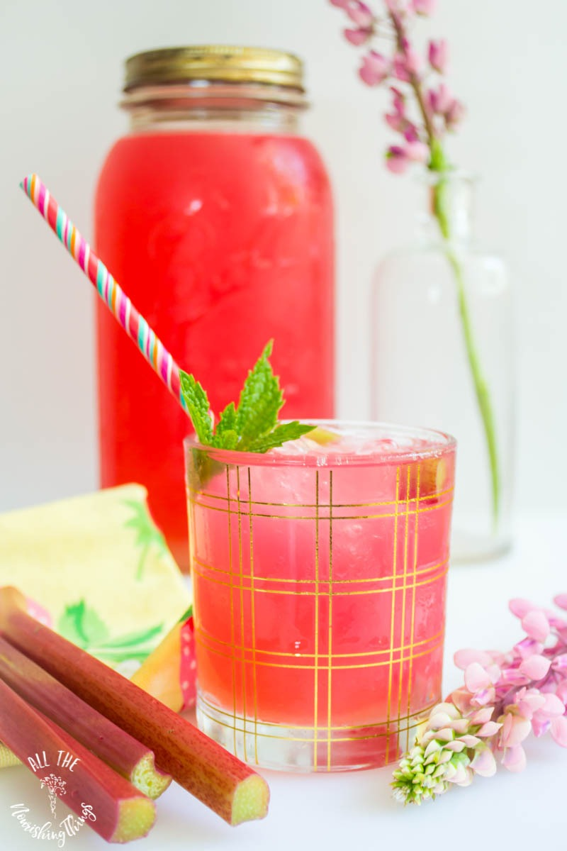 glass of instant pot rhubarb juice with pink-striped straw