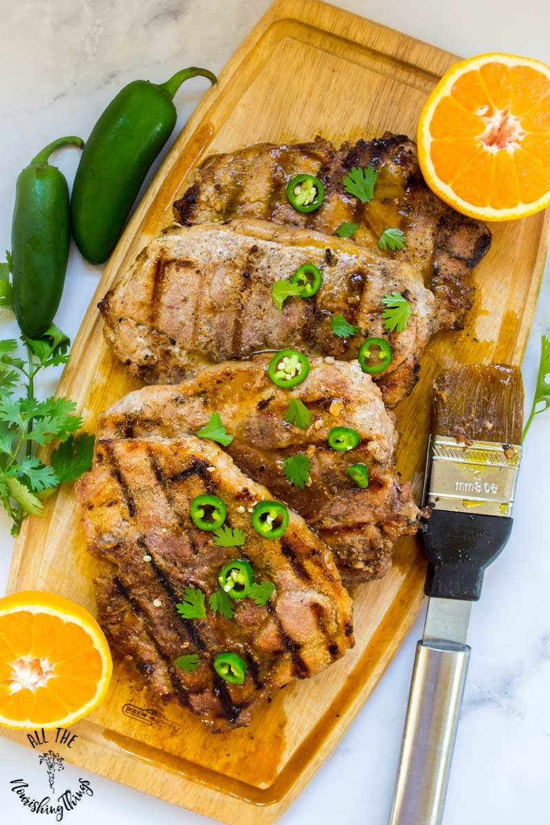 paleo grilled pork chops with orange-ginger-jalapeno glaze on wooden cutting board with jalapeno and orange garnishes