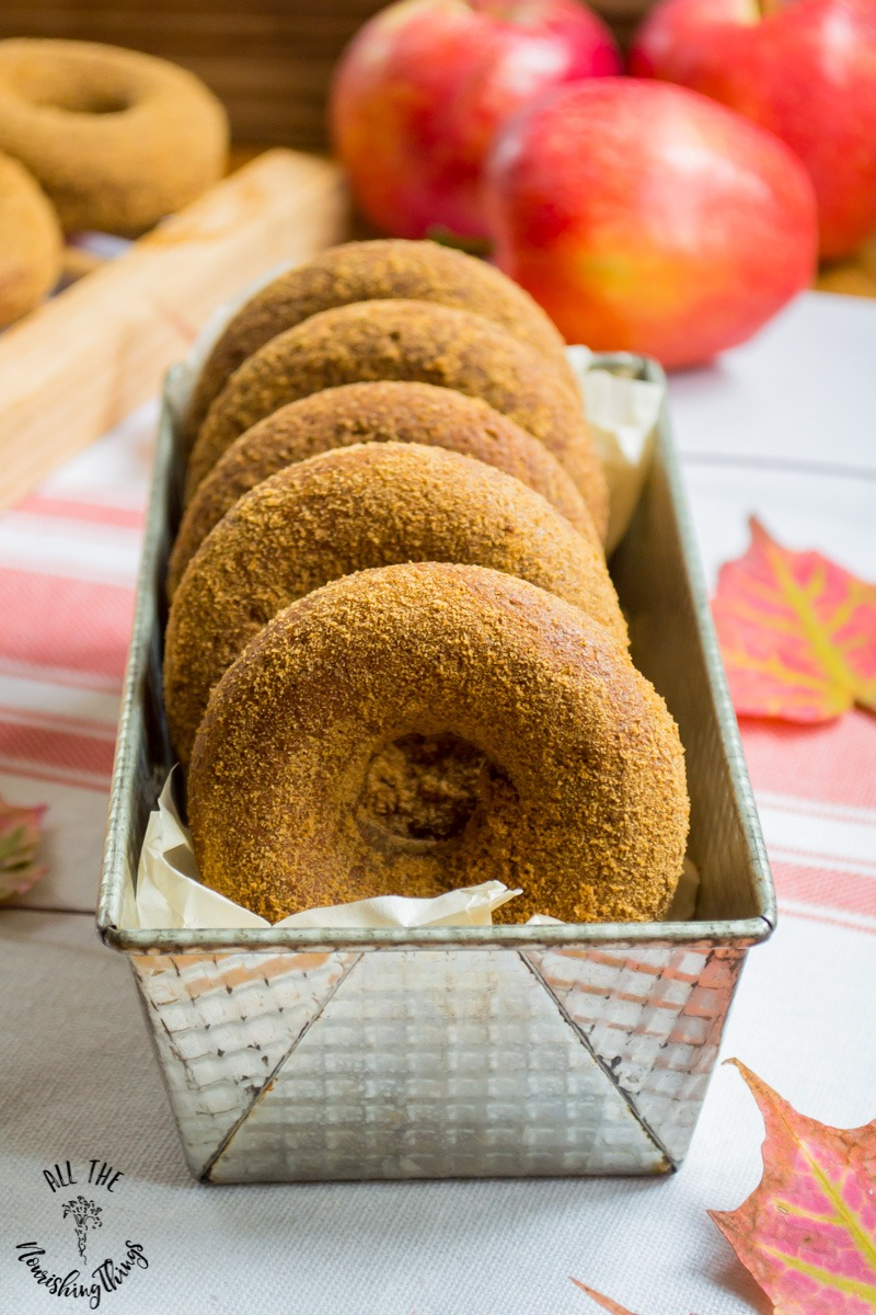 metal tin of gluten-free soaked apple cider donuts with apples in background