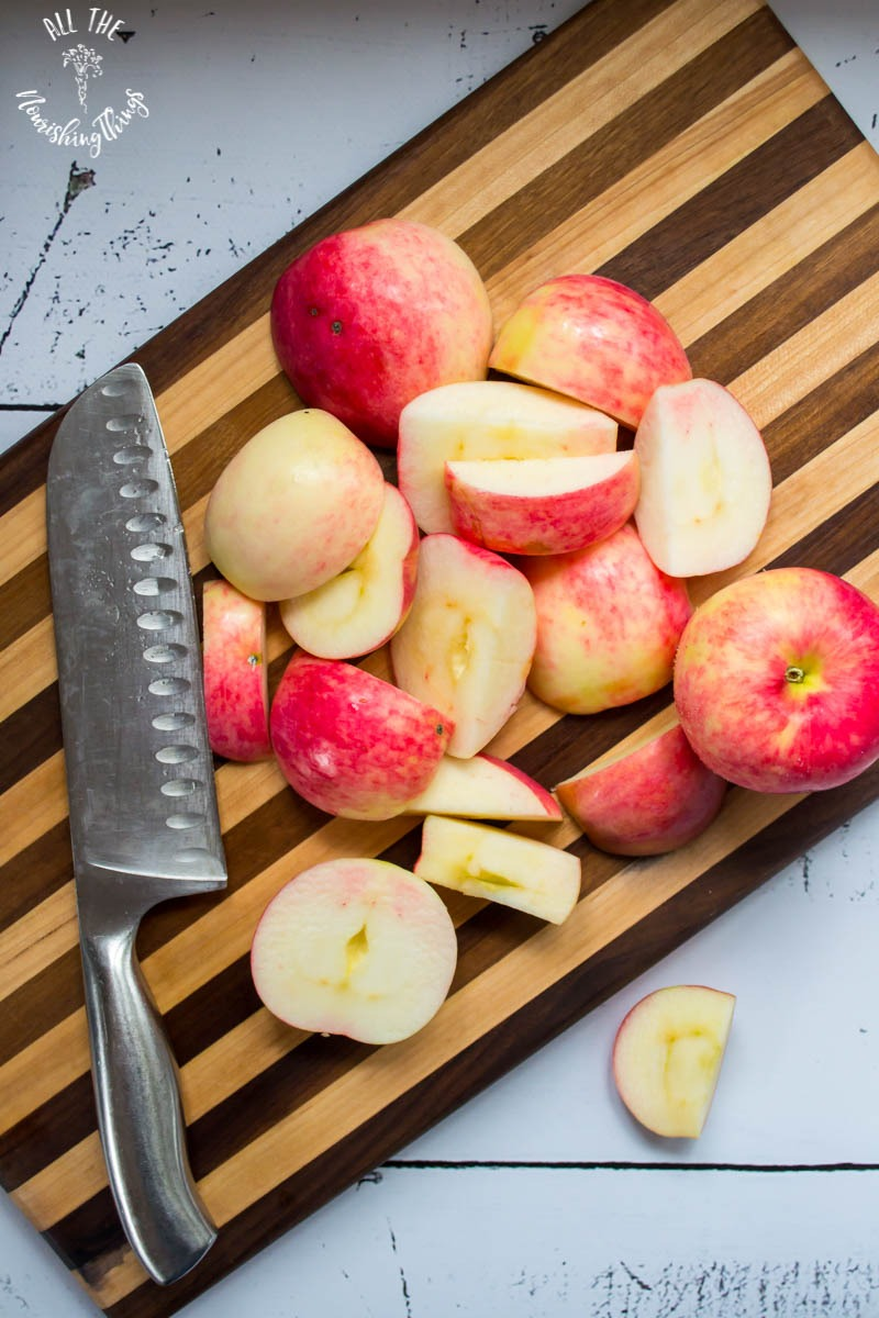 cut apples and knife on wooden cutting board