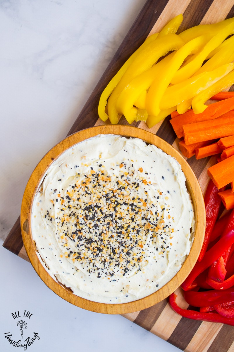wooden bowl of everything seasoning cream cheese dip with yellow and red peppers and carrot sticks