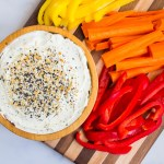 wooden bowl of everything seasoning cream cheese dip with cutting board of bright fresh vegetables