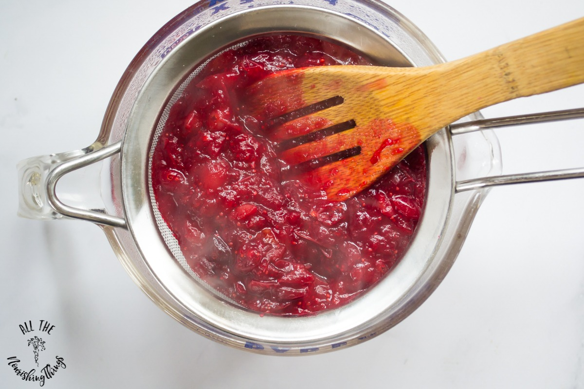 wooden spoon pressing cranberry puree through sieve