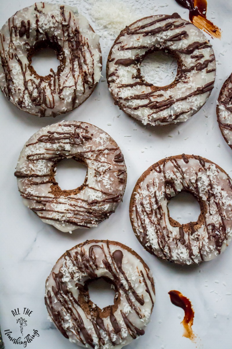 5 keto chocolate coconut donuts on marble countertop