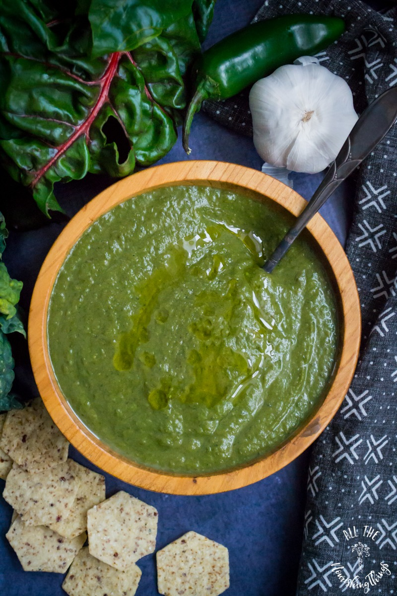 instant pot green soup in wooden bowl with a spoon and surrounded by greens, pepper, garlic, and crackers