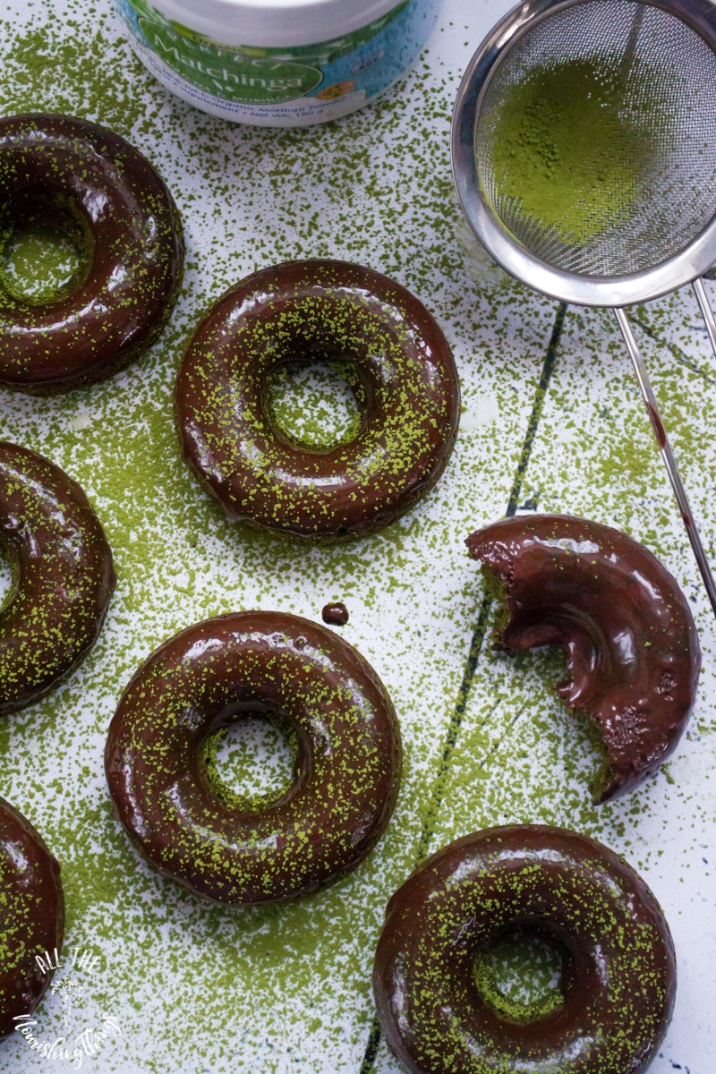 green matchinga powder on a sieve sprinkled on keto matcha-moringa baked donuts