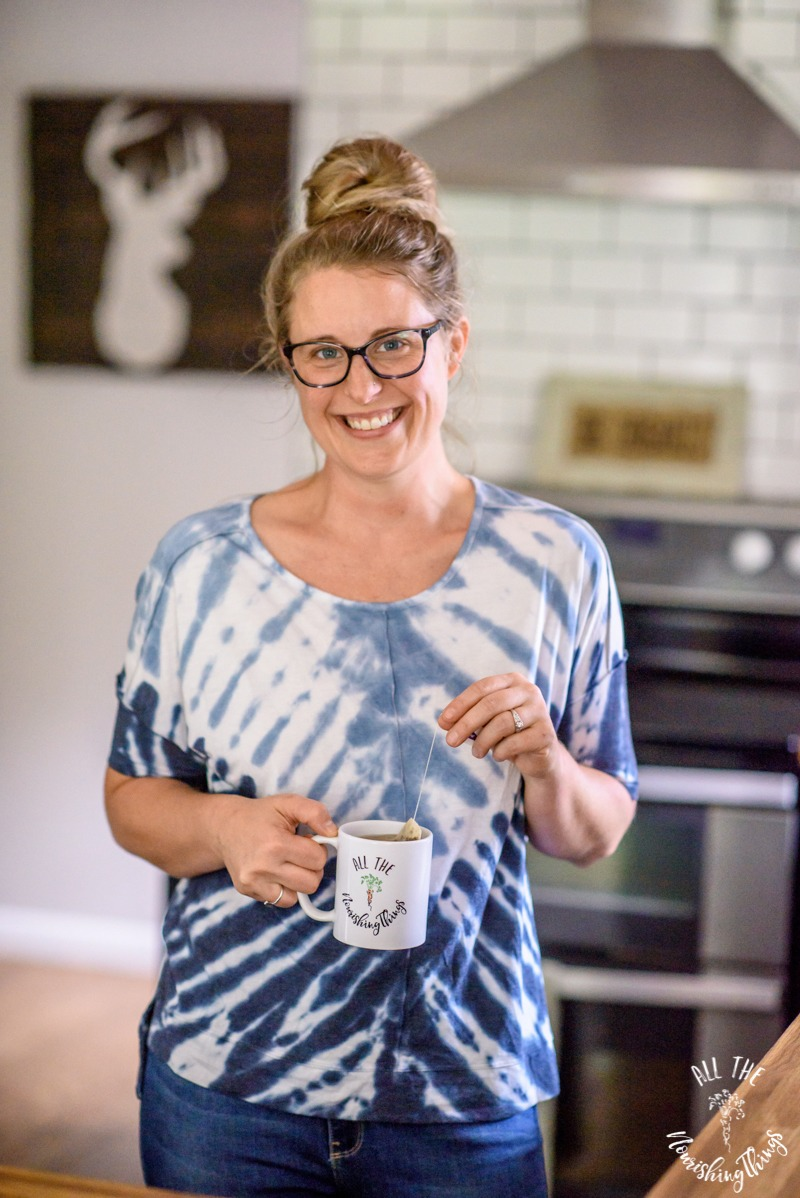 woman in glasses and blue tye-died shirt with a cup of hot tea