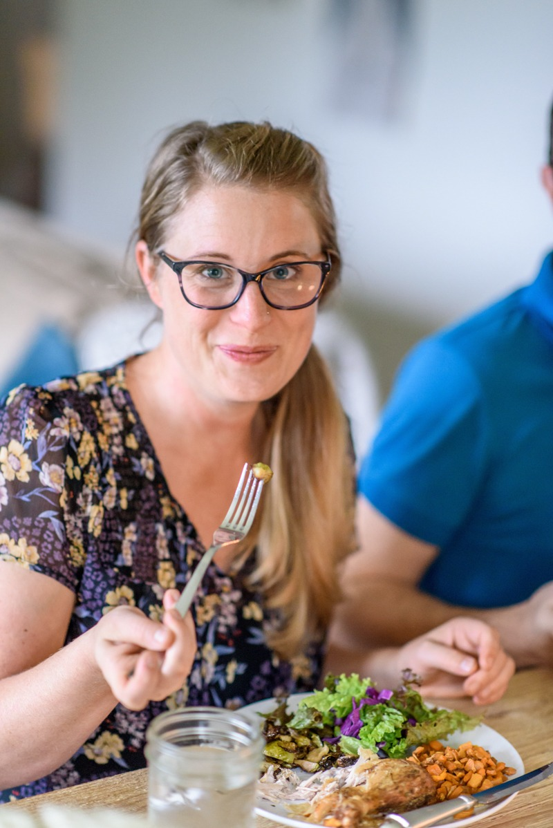 smiling woman eating brussels sprouts