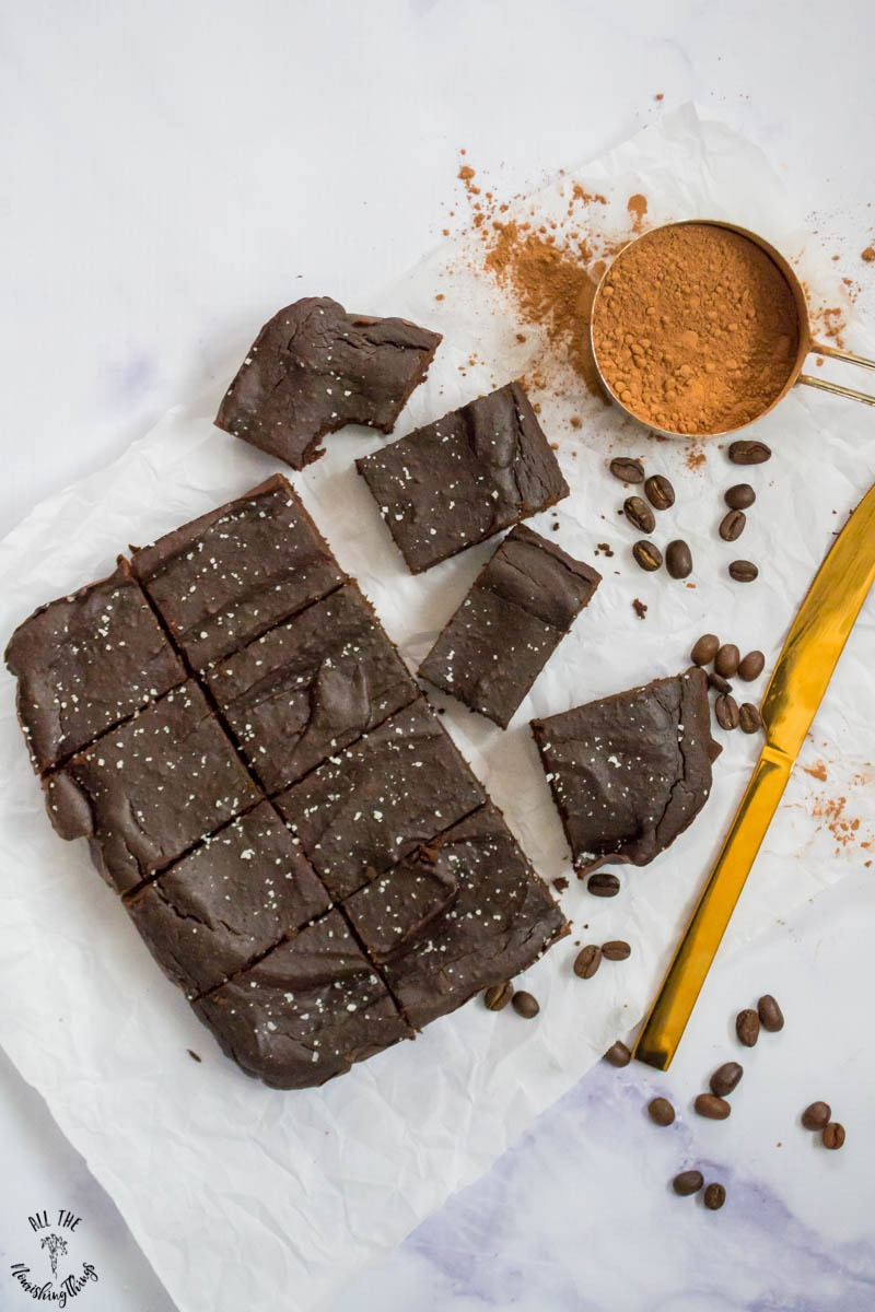 overhead view of salted caramel mocha fudge brownies on parchment paper and marble counter