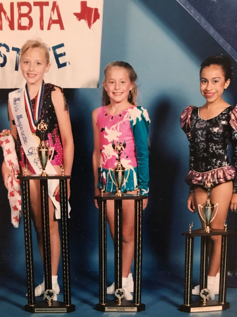 3 young baton twirlers with trophies