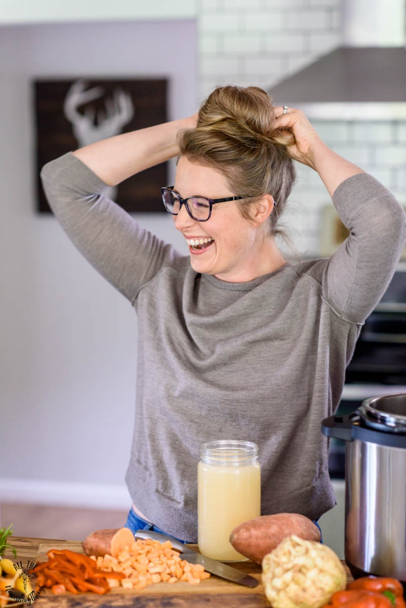 woman fixing her hair and laughing while standing in her kitchen