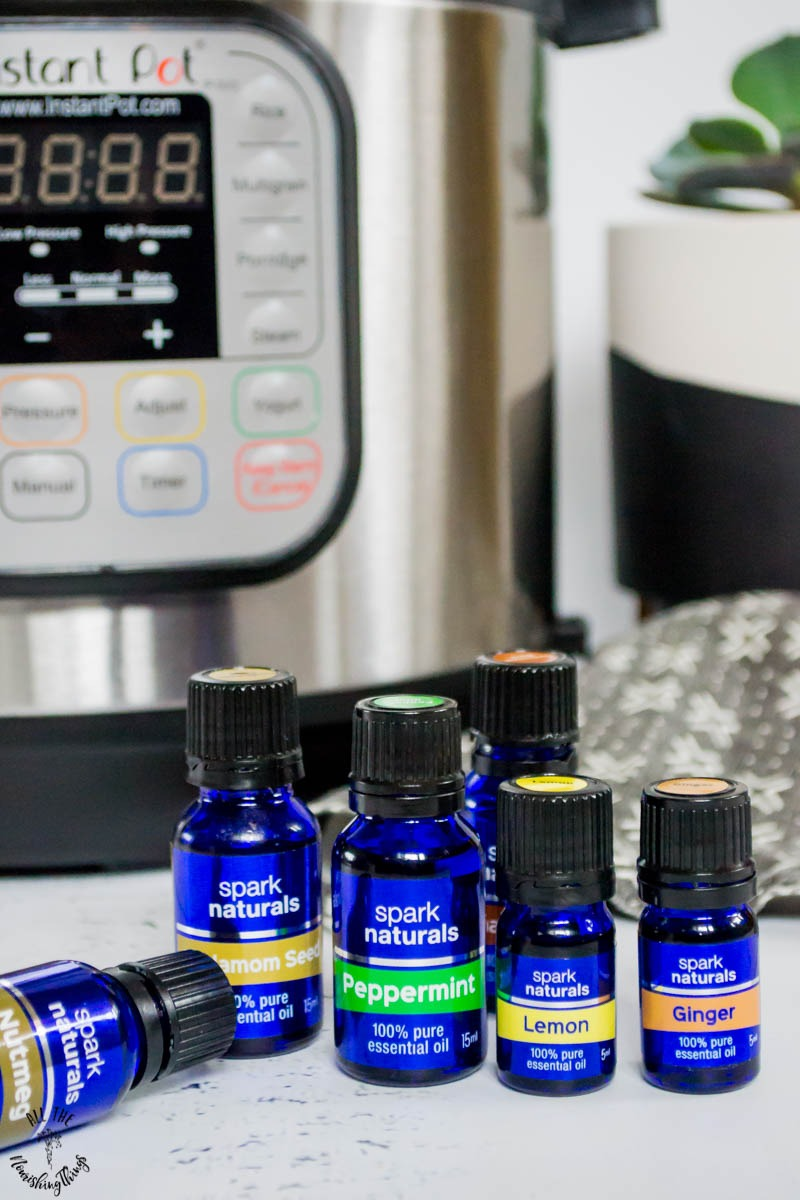 blue bottles of spark naturals essential oils lined up in front of an instant pot