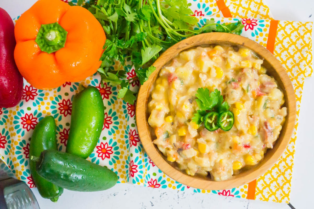 dairy-free instant pot bacon jalapeno corn chowder in a wooden bowl with a colorful tea towel and peppers