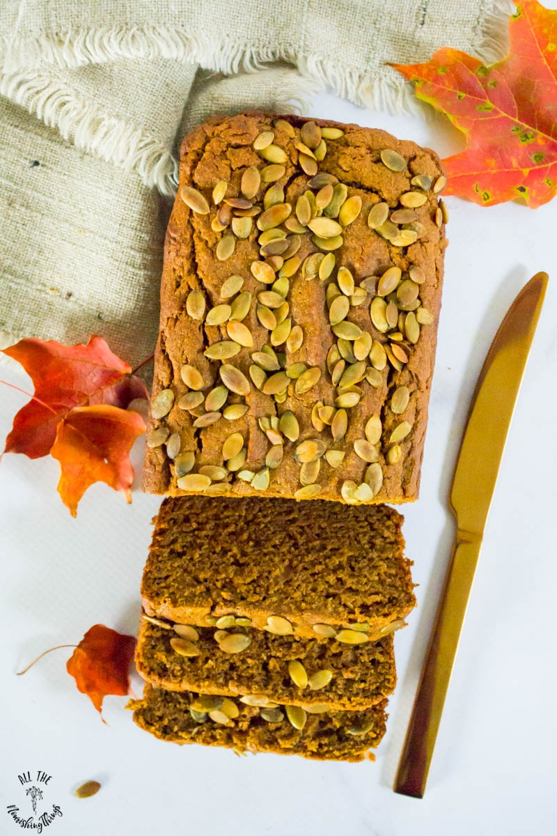 sliced cassava flour pumpkin bread with gold knife and orange maple leaves