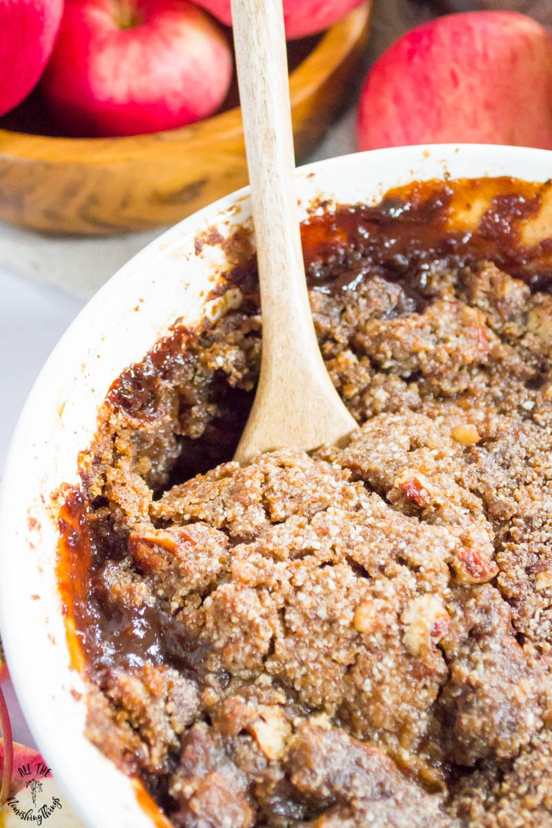 close-up of paleo instant pot apple pecan crumble with a wooden spoon