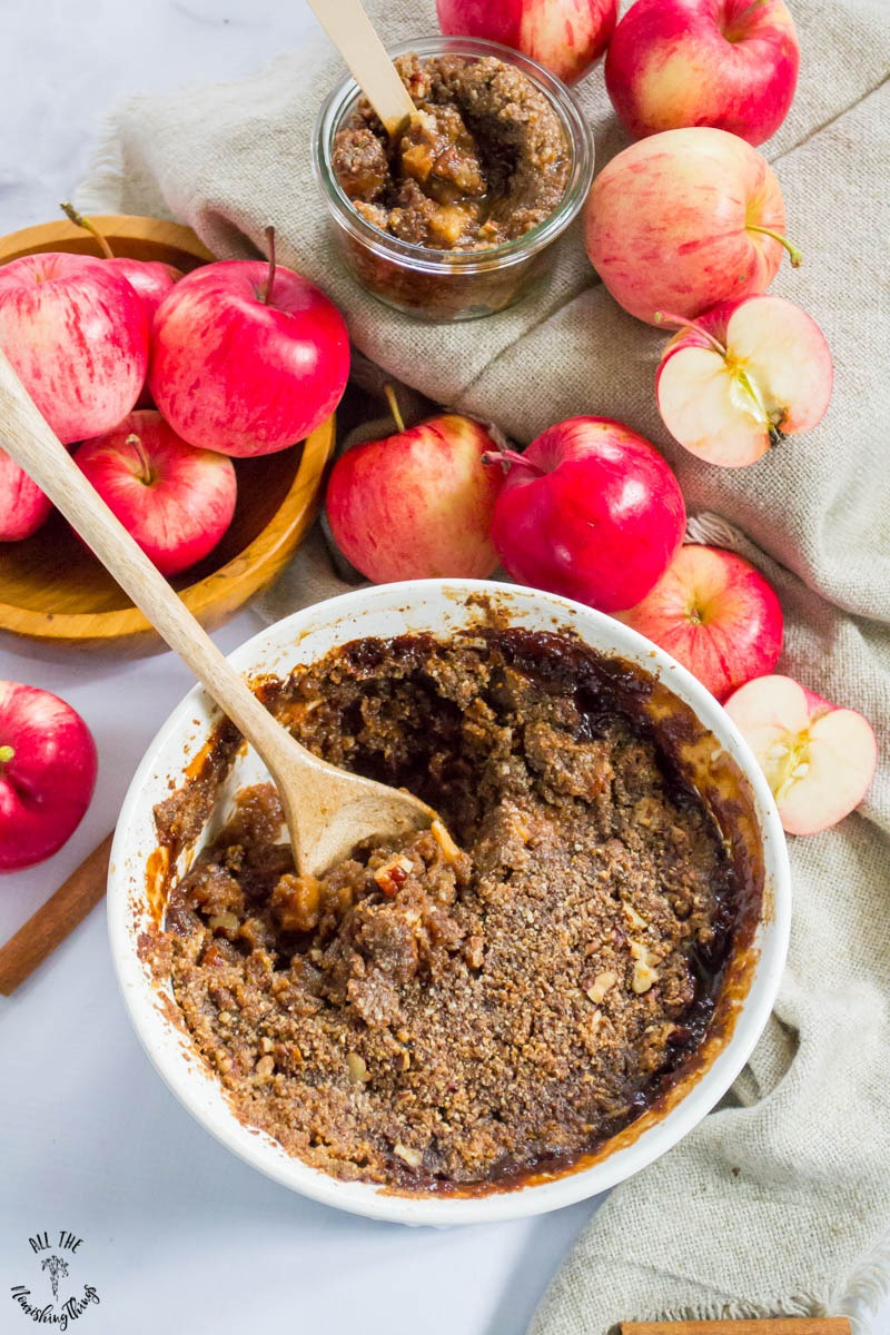 white baking dish of paleo instant pot apple pecan crumble with red apples and a wooden spoon