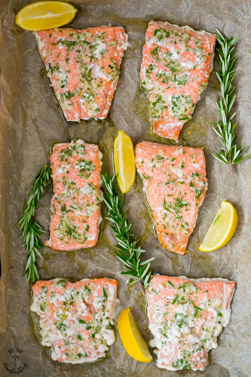 6 filets of sheet pan salmon with garlic and rosemary garnished with lemon wedges and rosemary sprigs