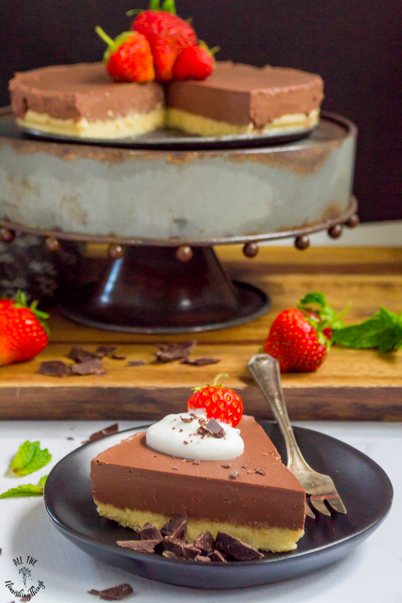 slice of vegan no-bake chocolate pie on a black plate sitting in front of the whole pie on a pie stand and garnished with strawberries