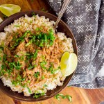 bowl of instant pot green chile pork topped with cilantro and a lime wedge