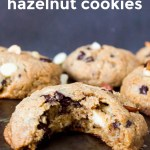 soft keto chocolate hazelnut cookies with a bite taken out of 1 cookie to show chocolate chunks and bits of hazelnuts