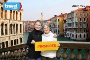 Two women in front of a fake background of Venice, holding a sign that says Inspired