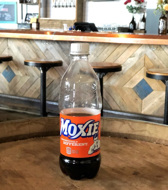 A plastic bottle of Moxie, a dark-colored beverage, sits on a wooden tabletop.