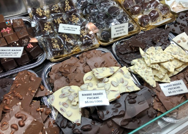 Two rows of various handmade chocolate candies in a glass case