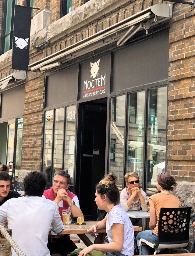 Several people sitting at ourdoor tables in front of a restaurant named Noctem