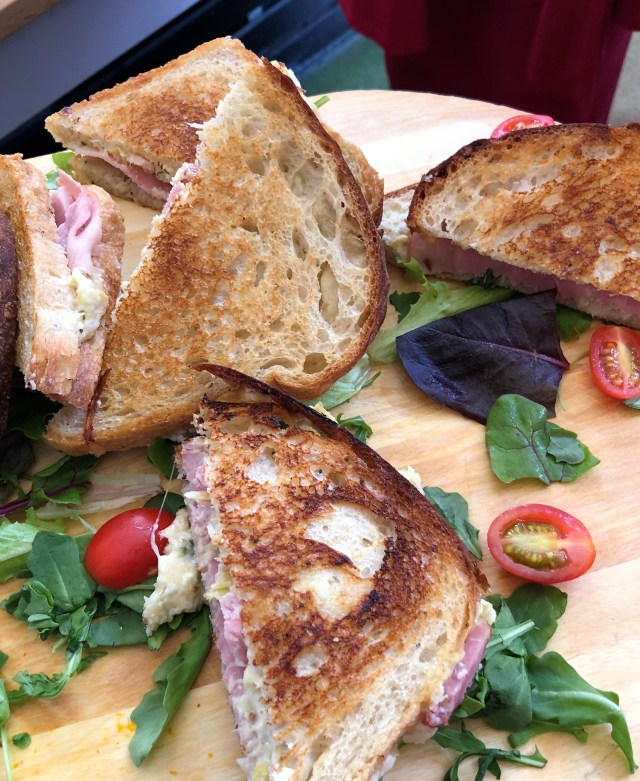 An arrangement of grilled cheese and ham sandwiches cut into triangles on a wooden board strewn with greens and grape tomato halves.