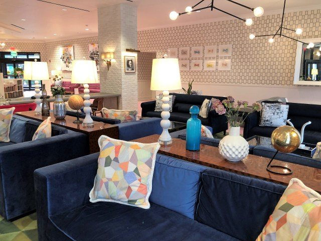 A hotel lobby segmented into seating areas for small-group conversation and lounging.