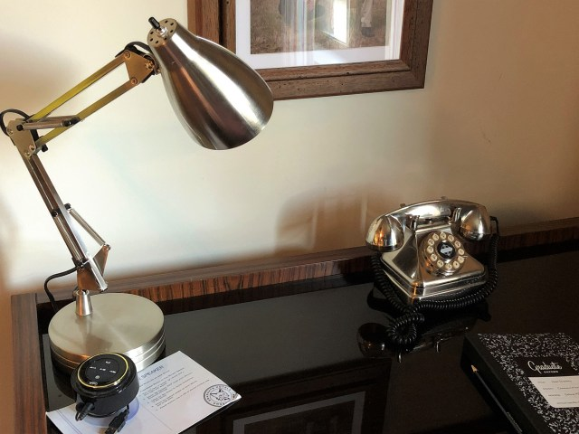 Closeup of a desk with silver retro telephone and silver gooseneck lamp