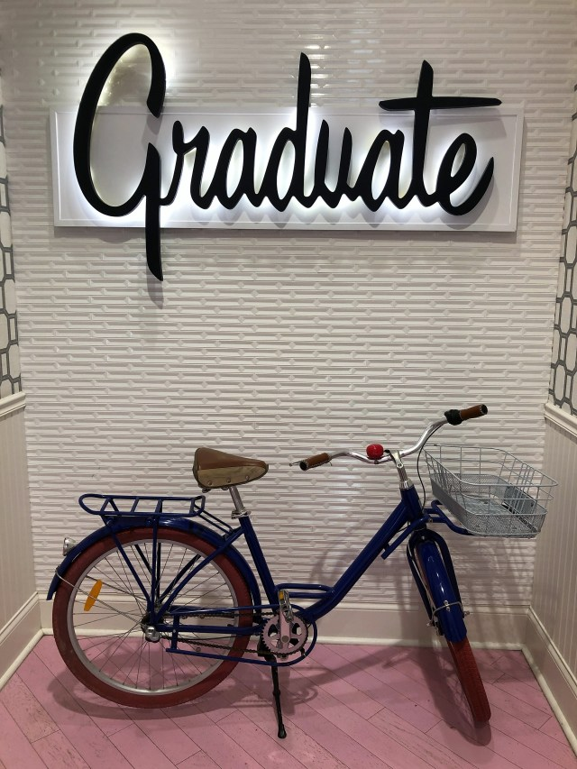 A navy bicycle parked against a white brick interior wall, the stylized sign above reads Graduate