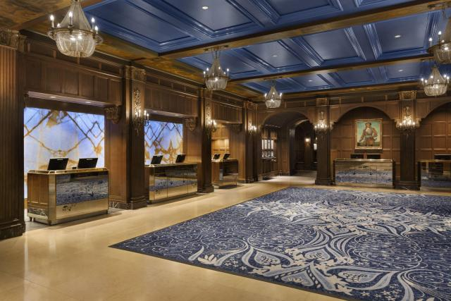 A massive hotel lobby with blue ceiling, marble floor and large blue-and-white area rug.