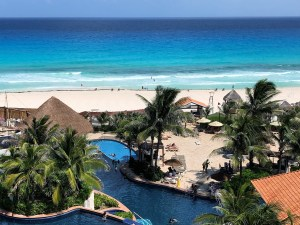 Overview of winding swimming pool and palm trees, beyond is sandy beach and vast ocean