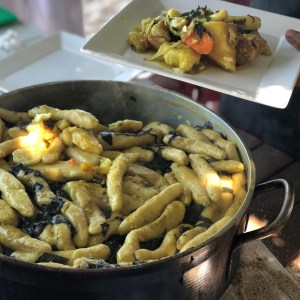 A silver pot with a layer of long, skinny dumplings on top, a plate with a scoop of Oil Down--a one-pot meal