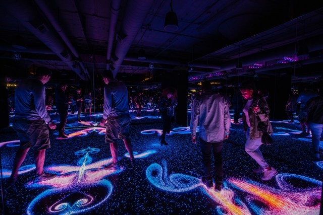 Several people walking in a darkened room, the floor lights up in swirls as they walk