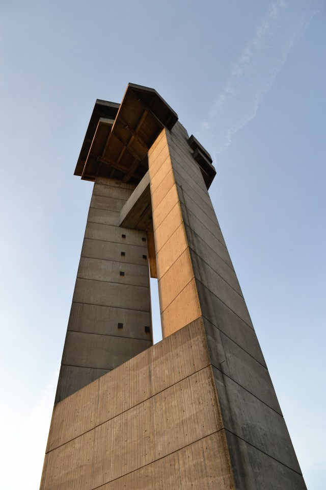 The top portion of a stone tower against a blue sky