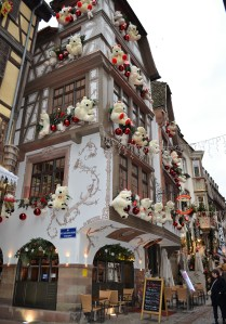 A white building with white teddy bears and red shiny balls affixed to the windows