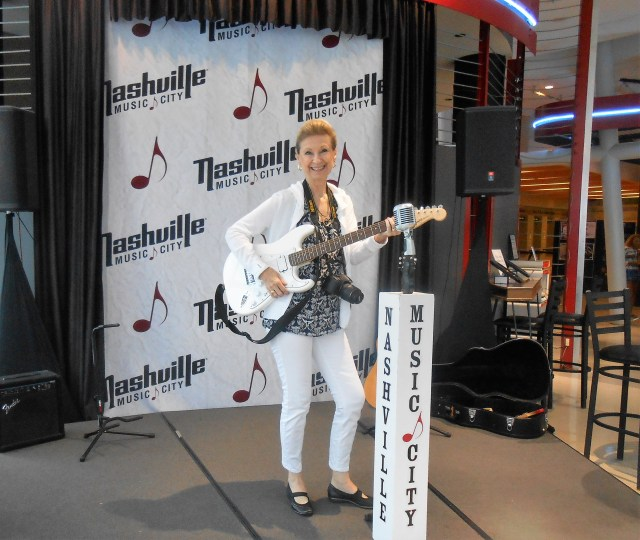 A woman (the author) stands on a small stage and holds an electric guitar.