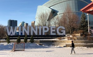 Giant outdoor letters spell out Winnipeg; an ice-skating rink in front with a lone hockey player