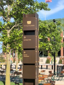 A vertical directional sign in an outdoor plaza with seating