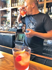 An Old-Fashioned cocktail sits on a bar, behind is a bartender drinking an Old-Fashioned cocktail.