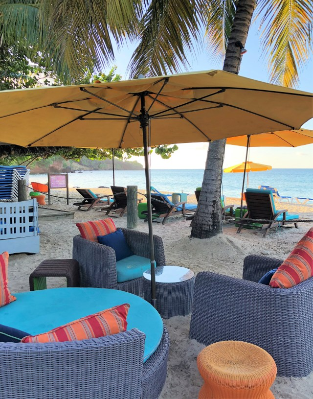 Wicker beach chairs and side tables beneath an umbrella on the beach